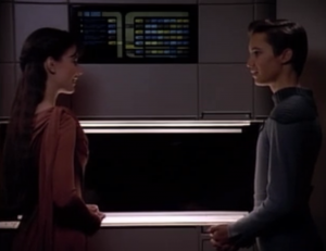 Wesley goes to Salia's door and stands there like an idiot. He looks like an idiot in front of a security guard. Salia saves him by asking him to come in to show her how to use the food replicator. Wesley goes on to explain how simple it is.