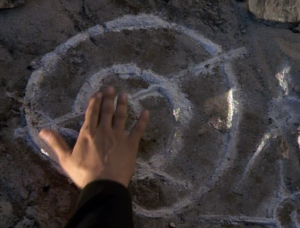 Chakotay sees a symbol drawn on a moon. Waving his hand over it helps him to see it better