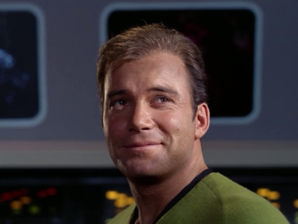 Kirk pretends like he's ok so that Spock will give up command and do the operation