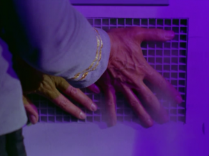 The smoke starts coming in through a vent a Spock tries to hold it back with his hands. He may have had a slight misjudgment on the size and shape of his hands