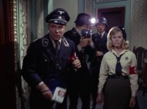 They meet up with a lady and she sneaks them into an event to see the fuhrer by them pretending to be her film crew. Hey, is this Inglorious Basterds?