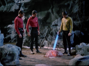 Chekov get's locked outside of the cave, and for some reason doesn't go back to Enterprise. They just wait around and start shooting rocks