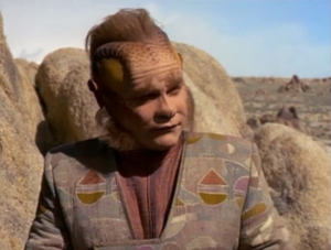 """The crew splits up into teams. I wouldn't want Neelix as my team leader. He asks Hogan to collect bones that they find outside of a cave. Hogan looks really scared and Neelix asks """"Is there a problem?"""" Neelix walks away and Hogan get eaten"""