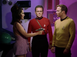 For a minute the space lady has a phaser, but then Scotty pretends to faint and Kirk grabs it