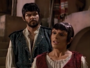 Riker and Troi go to the planet in disguise. Riker looks especially stupid