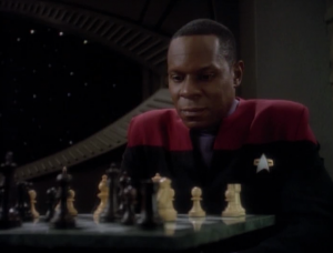 Dax and Sisko play old 2D chess, but Dax accuses Sisko of cheating and knocks over all the pieces.