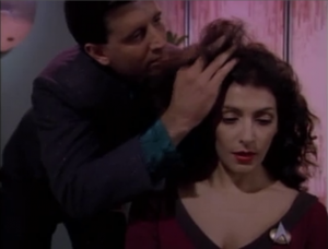 A guy messes with Troi's hair.