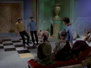 They want Bones to stay with them in case someone else get's a cut. To persuade Bones they humiliate Kirk and Spock until he agrees. First there is dancing