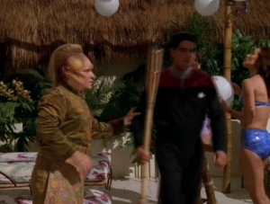 Neelix and several other crew members are hard at work decorating a holodeck program. I don't think they quite understand how a holodeck works. Just tell it to have those decorations