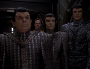 The Romulans come aboard. They want the intel Starfleet promised in exchange for the cloaking device on the Defiant
