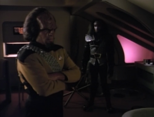 Turns out it's his little brother. Their father is being accused of being a traitor. Worf must go to the Klingon home-world and challenge the ruling.