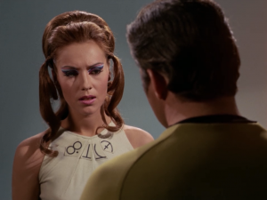 Kirk shows the lady the mask, and explains how it will make her people less dumb