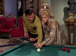 She teaches Kirk how to play pool. Hey Kirk, isn't your whole crew dying or something?