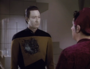 The really wants Data to wear different clothes, but Data refuses, so he throws some kind of acid on Data that will burn up the uniform