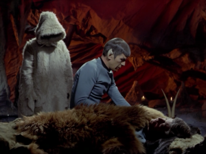 A hooded person leads Bones and Spock to a cave
