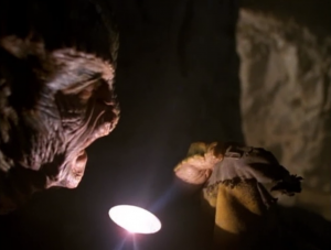 "A lizard guy is digging through the cave from ""Basics."" He finds the remains of the Voyager guy that was killed"