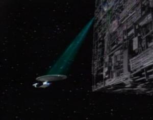 The Borg take out their shields and start cutting into the ship